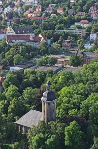 Blick auf die Kirche im Johannisfriedhof und die dahinter liegenden Gebäude von Uni und Uni-Klinikum.