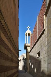 Schmaler Durchgang zwischen hohen Mauern im koptischen Kairo, mit einem Eingang zu einem koptischen Heiligen-Grab.