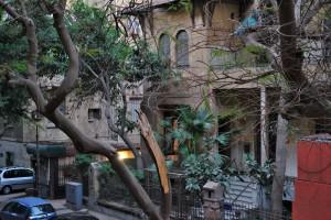 Blick vom Balkon am Schlafzimmer auf ein gegenüberliegendes altes Gebäude und einen halben Baum.