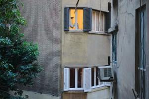 Blick aus dem Wohnzimmer über den Hinterhof auf das nächste Wohnhaus. Oben ist das Ende eines dort an Kabeln hängenden Astes zu sehen.