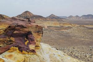 Schwarze Wüste mit violettem Felsen im Vordergrund