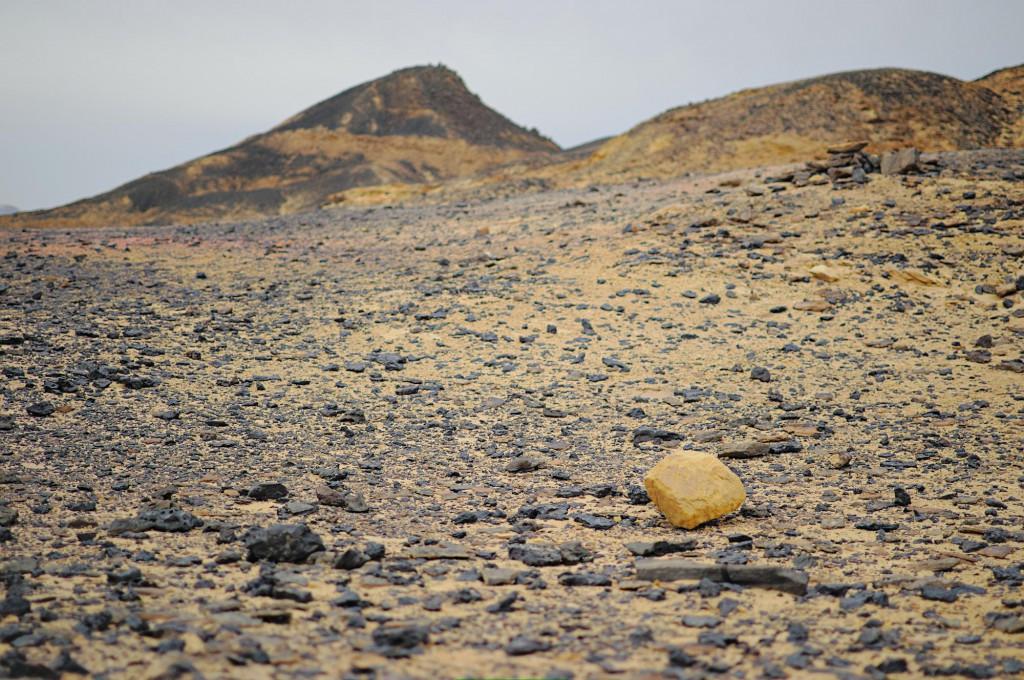Ein einzelner gelber Felsblock in der schwarzen Wüste.