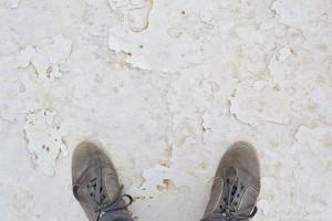 Glatter weißer Wüstenboden mit meinen Schuhen.