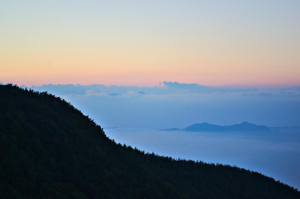Einzelne Berggipfel in der Umgebung des Fuji in Wolken getaucht.