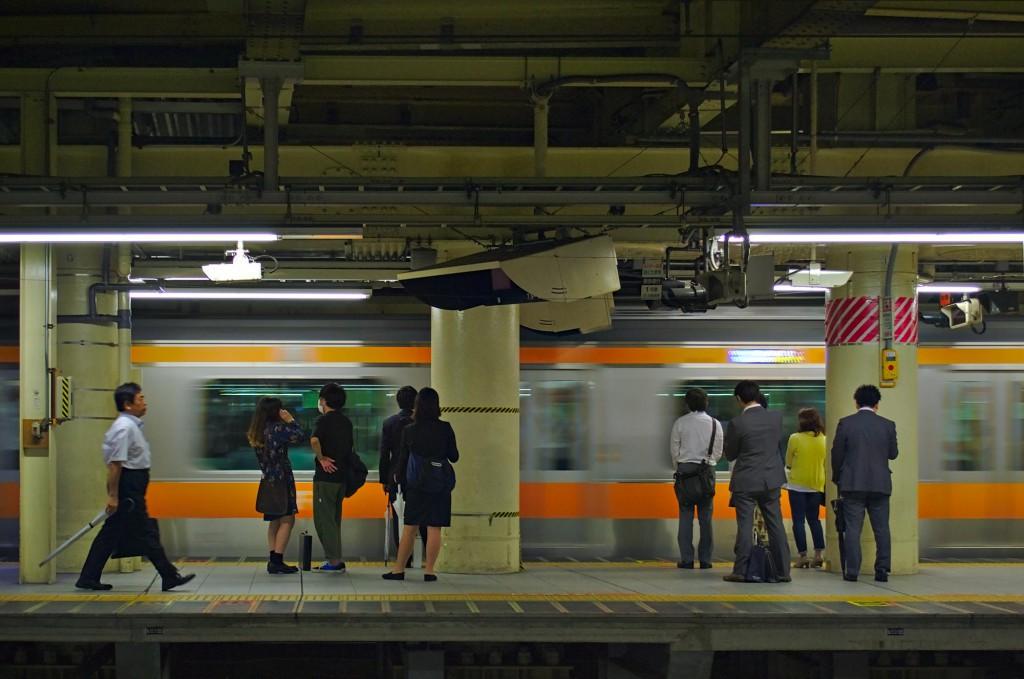 Menschen warten auf den Zug am Bahnhof Shinjuku in Tokio, während der Zug einfährt.