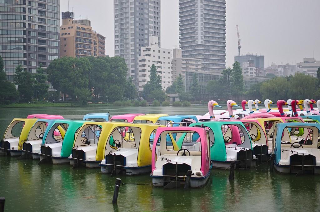 Tretboote, darunter Schwan-Boote in kitschigen Farben auf einem Teich in Tokio vor Hochhäusern.