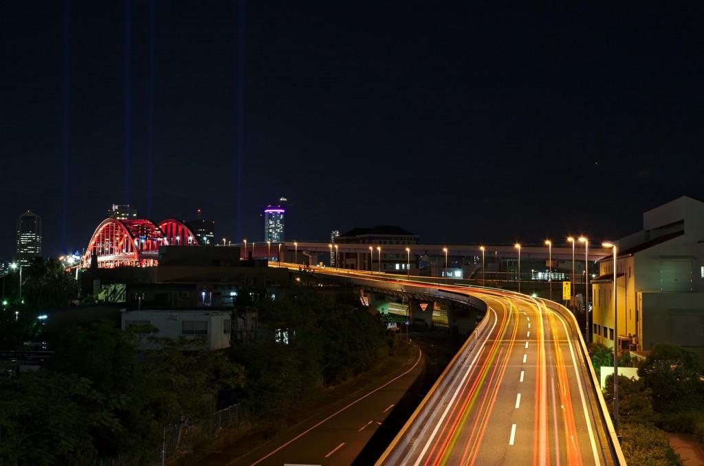 Brücke mit Leuchtspuren von Autos zum Festland von einer künstlichen Insel in Kobe.