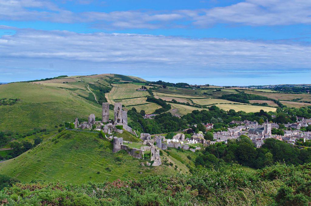 Corfe Castle und das angrenzende Dorf von einem benachbarten Hügel aus.
