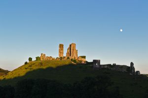 Corfe Castle im Abendlicht, schon halb im Schatten des benachbarten Hügels.