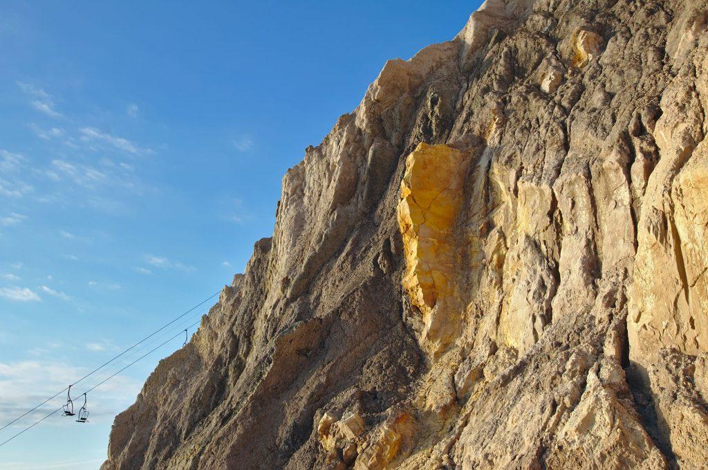 Gelbe Felsscheibe zwischen dunklerem Gestein in der Alum Bay