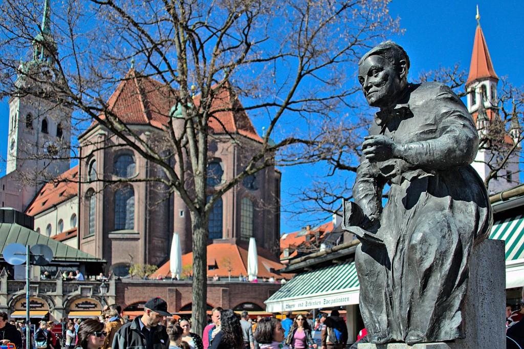 Eine kleine Statue zwischen den Ständen auf dem Viktualienmarkt in München.