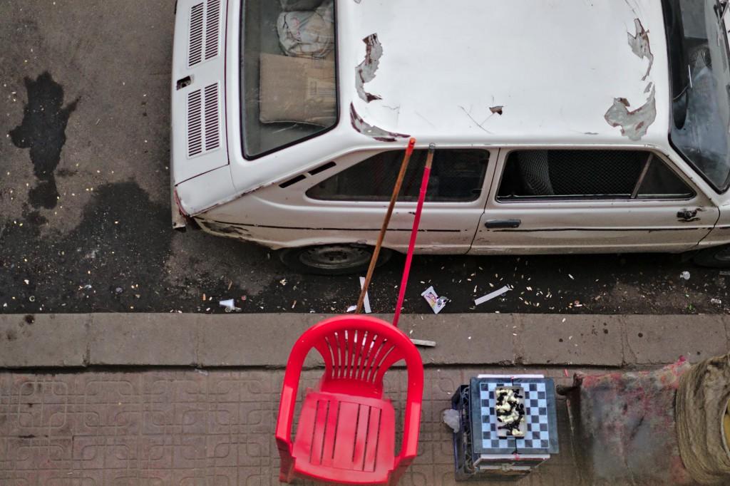 Blick vom Balkon auf den Bürgersteig, wo sich die Männer aus dem kioskartigen Laden im Erdgeschoss mit Brettspielen die Zeit vertreiben.