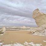 Ein kleiner Pinguin-Fels betrachtet einen größeren Felsen in der Weißen Wüste.