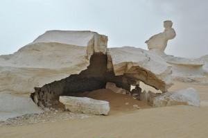 Eine kleine Höhle im Vordergrund. Im Hintergrund sieht man den Hasen der Weißen Wüste.