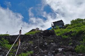 Lavafelsen mit Seilen, die den Aufstiegsweg zu einer Hütte im Hintergrund markieren.