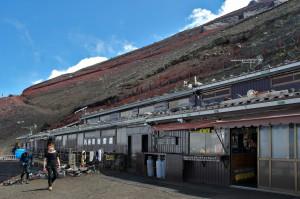 Eine Verpflegungsstation am Fuji. Robust gebaute Hütte vor einer Schräge aus roter und schwarzer Lava.