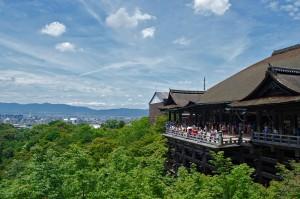 Haupthalle und die berühmte Holz-Terrasse des Kiyomizu-dera Tempels in Kyoto mit der Stadt im Hintergrund.