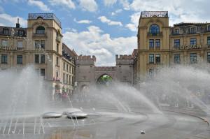 Das alte Stadttor am Karlsplatz (Stachus) in der münchner Innenstadt mit einem Springbrunnen im Vordergrund.