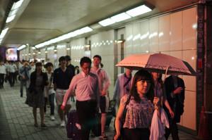 Passanten in einer Bahnunterführung in Tokio, im Vordergrund eine Frau mit Schirm, den Tunnel verlassend.