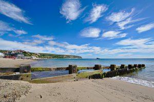 Der Strand von Swanage an der englischen Kanalküste mit einem Holzdings im Vordergrund, das Sand am Strand festhalten soll.