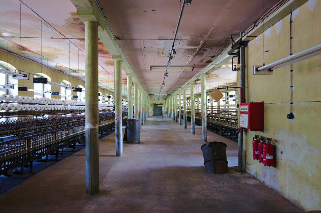 Eine lange Reihe von Maschinen zum verzwirnen von mehreren Fäden zu einem neuen.