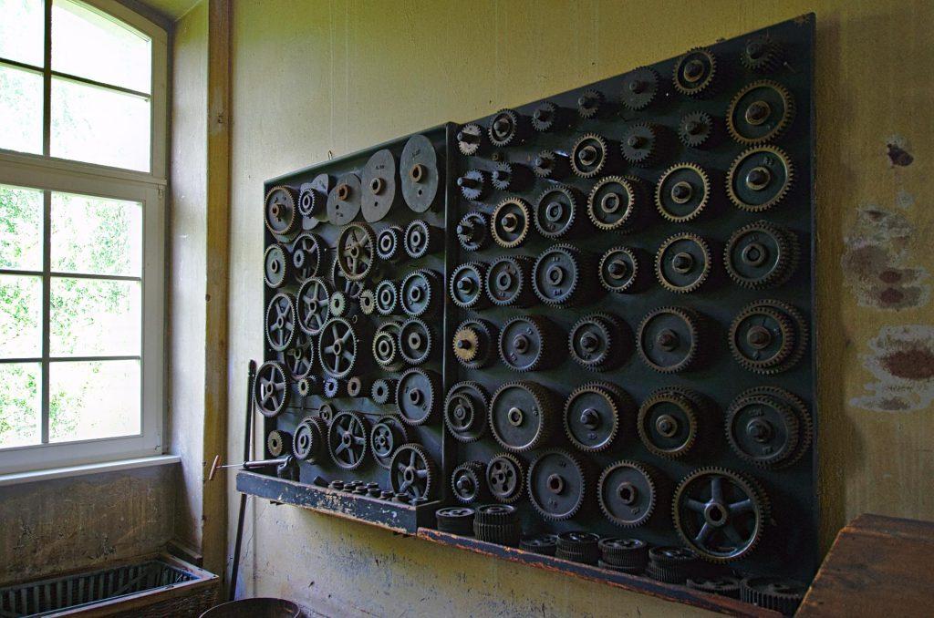 Überall an den Wänden gibt es Sätze von Zahnrädern, um die Maschinen an verschiedene Garne oder Stoffe anpassen zu können.