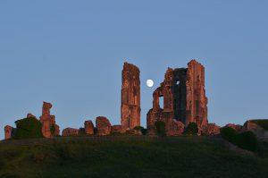 Der Mond zwischen den Ruinen von Corfe Castle im Licht des späteren Abends.