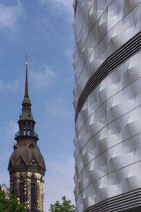 Kirchturm neben der Fassade eines Einkaufszentrums am Richard-Wagner-Platz in Leipzig
