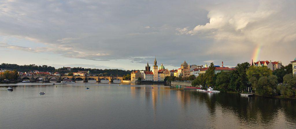 Blick flussabwärts auf die Karlsbrücke und einen Regenbogen über der Altstadt von Prag.