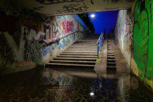 Überflutung in einer Unterführung, die Treppe zum Ausgang ragt aus dem Wasser.