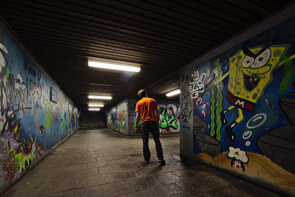 Spongebob-Grafitti in einer Unterführung mit einem Menschen, der um eine Ecke des Tunnels guckt.