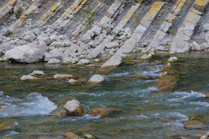 Schräg verlaufenden Gesteinsschichten an einem Fluss in den französischen Alpen
