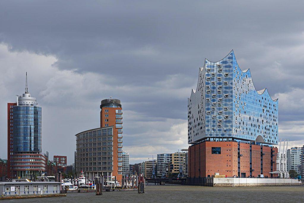 Blick von einer ÖPNV-Fähre auf die Elbphilharmonie und zwei benachbarte Hochhäuser.