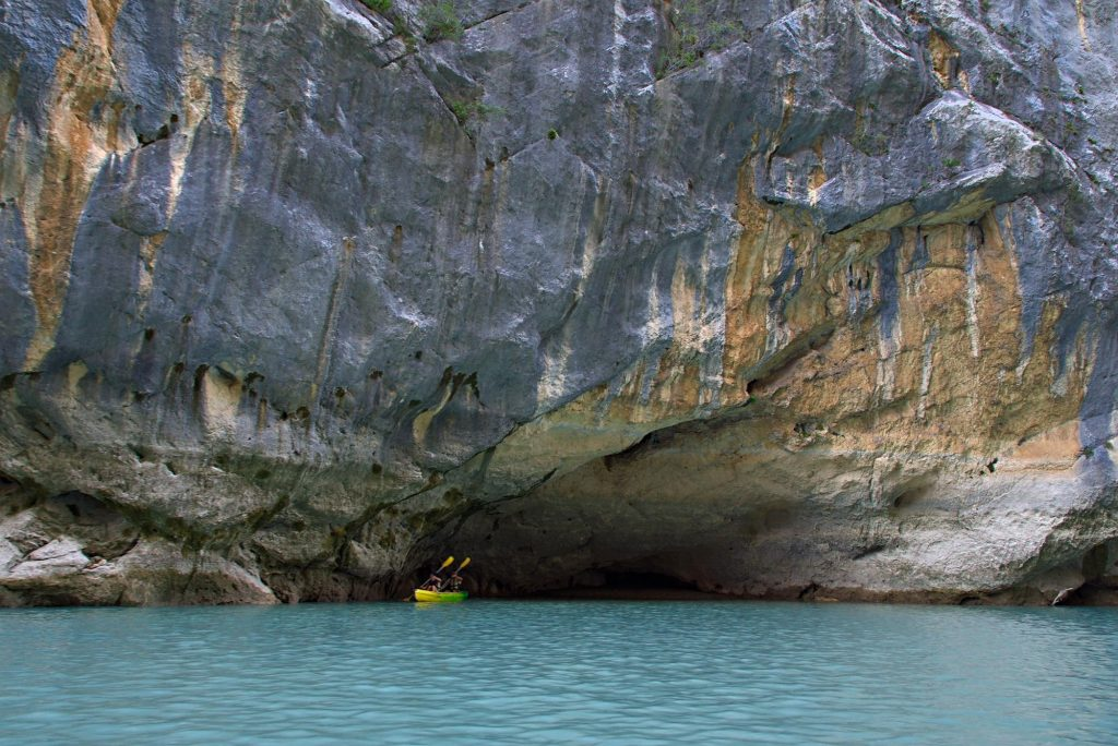 Ein Paddelboot auf der Verdon unter einer großen Felswand.