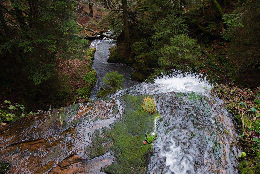 Das obere Ende des Sankenbach-Wasserfalls, wo sich das Wasser schäumend über die Klippe stürzt.